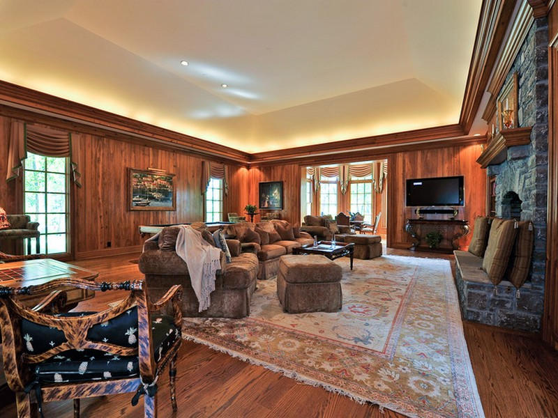 An impressive stone fireplace serves as an anchor in the paneled living room with a coffered ceiling, beautiful hardwood floors and plenty of room to spread out for a rousing game of chess or to enjoy a movie on the flat screen.